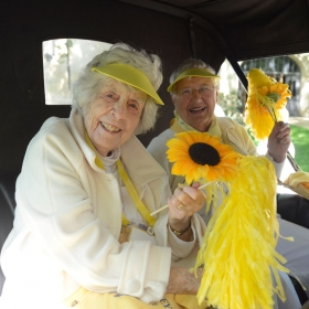 Two class of 1942 alumnae sit in an antique car, holding sunflowers