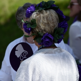 A class of '62 alumna wears purple flowers in her hair