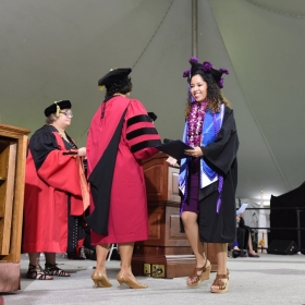 A student wearing a tam decorated with purple flowers crosses the stage after receiving her diploma.