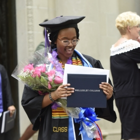 After the ceremony, a student stands on the steps of Clapp Library, clutching her diploma and a bunch of flowers.