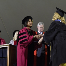 A photo of President Johnson awarding a diploma to a student