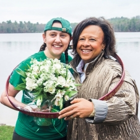 Laurel Wills '17 and President Paula Johnson pose inside Laurel's hooprolling hoop as Laurel holds a bouquet of flowers.