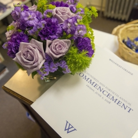 A photo of a bouquet of purple roses beside the commencement program.