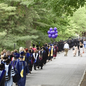 A photo of the faculty processing in to Commencement, seen from the back.
