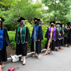 Students in line before Commencement 2021, wearing robes and stoles and masks