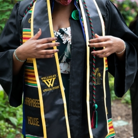 A student adjusts Harambee House and Africana studies stoles before commencement