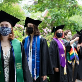 Students in line before commencement, wearing robes and stoles and tams