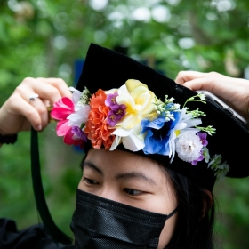A student adjusts their tam, decorated with a colorful wreath of flowers, at commencement