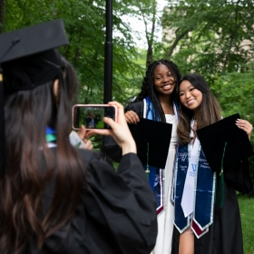 A student uses their cell phone to take a picture of two other students embracing and smiling for the camera
