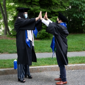 Two students in robes and tams high-five with both hands