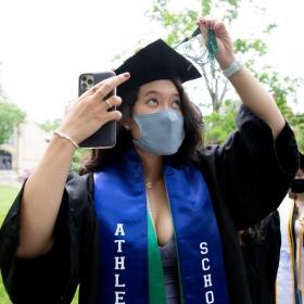 A student adjusts their green tassel