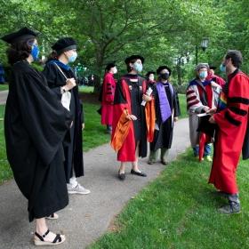 Faculty members in regalia joshing around