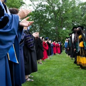Faculty applaud as students process during commencement