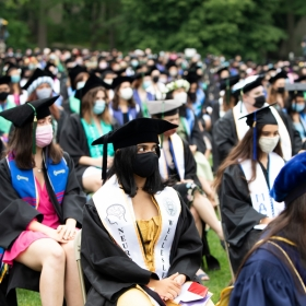 The students sitting at commencement, wearing masks