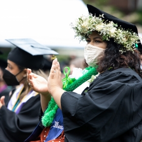 A student with a white wreath of flowers around her tam applauds at commencement