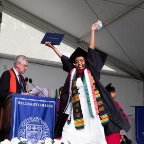 A student celebrates after receiving their diploma