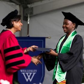 Paula Johnson hands a diploma to a graduate