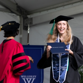 A student grins receiving their diploma
