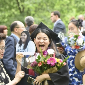 A laughing graduate clutches her flowers and diploma.