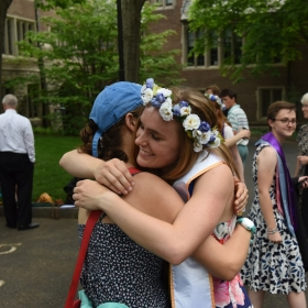 A photo shows two students grabbing a final hug after reunion.