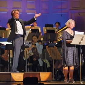 A photo shows Keith Lockhart, conductor of the Boston Pops, with astronaut Pam Melroy '83, during a concert celebrating the anniversary of the moon landing in 1969.