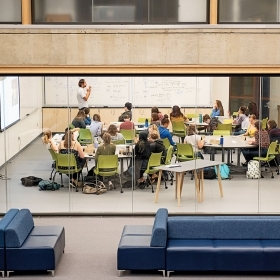 A professor teaches a course in a new classroom by the data lounge.