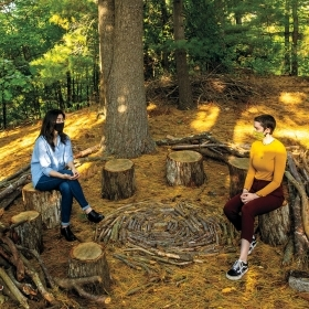 Valeria Yang '21 and Bryn van Dommelen '22 sit on tree stumps in the Sitting Circle in golden early fall light