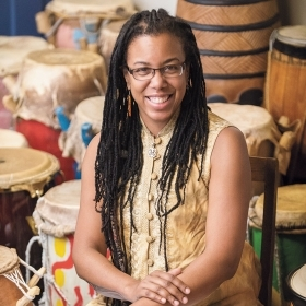 Kera Washington '93 sits among the African drums that Yanvalou members play.