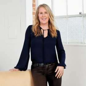 A photo of Susan Genco '88 standing in a modern, white-walled room