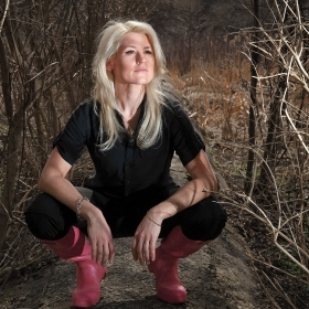 Anne Madden, wearing red rain boots, crouches in a field