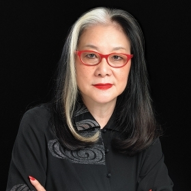 A photo of Mee See Loong '72, wearing black, with red-framed eyeglasses and a dramatic red ring on her hand.