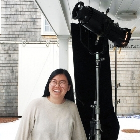 Cathy Ye '19 stands next to professional lighting equipment.
