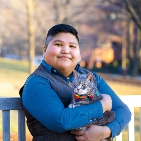 A portrait of AJ Guerrero, Wellesley's coordinator for LGBTQ+ programs and services, holding her cat
