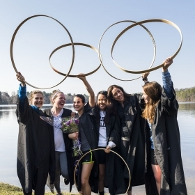 Hooprolling champion Emmy Hamlton '18 and five friends lift their hoops in this photo taken on the shore of Lake Waban