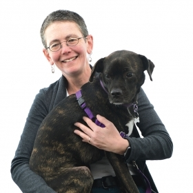 Beth DeSombre sits with her dog on her lap.