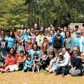 A photo of a large group of alumnae gathered in a park to celebrate the Atlanta Wellesley Club's 80th birthday.