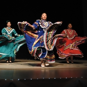 A photo shows three students, members of Cielito Lindo, Wellesley's Latin dance organization, performing a Mexican ballet folklórico, wearing bright costumes that reflect Spanish and indigenous influences.