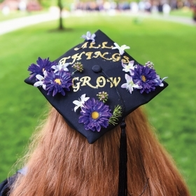 "A student wears a tam decorated with flowers and the phrase ""All things grow"""
