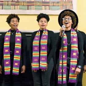 A photo shows members of the Harambee Singers, wearing kente-cloth stoles, performing.