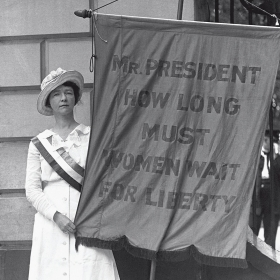 "A suffragist holds a banner reading ""Mr. PRESIDENT HOW LONG MUST WOMEN WAIT FOR LIBERTY"""