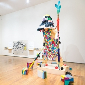 Survival Robot (2020), a two-story tall humanoid figure holding two colorful staffs and wearing a shift made of colorful, pieced-together shapes, surrounded by smaller colorful boxes