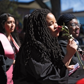 A student holds a rose to her face at the student-organized graduation ceremony in March.