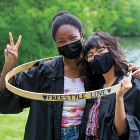 """Tendayi Peyton '21 and Izabelle Fernandez '21 pose inside a hoop reading """"Freestyle Love."""" Both are wearing masks and graduation robes."""