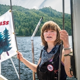 """A photo of Elsa Sebastian on the deck of a boat holding a """"Save the Tongass"""" flag"""