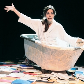 Marta Rainer '98 sits in a bathtub on stage surrounded by books as part of her one-woman show