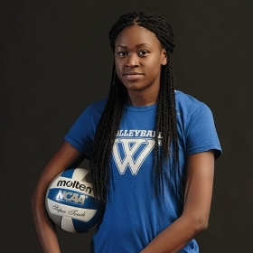 Portrait of Yasmine Reece '19 in her volleyball uniform, holding a volleyball.