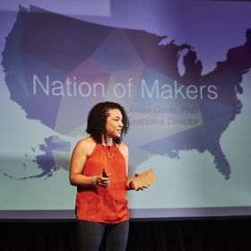 "A photo shows Dorothy Jones-Davis '98 speaking in front of a large map of the United States with the words ""Nation of Makers"" emblazoned across it."