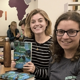 """A group of young alums sitting around a table hold up their copies of """"Little Fires Everywhere"""""""