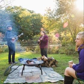 A photo shows Alden Griffith and Kim McLeod on guitar and mandolin serenading a listener around a campfire beside Paramecium Pond