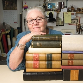 A photo portrait shows Betsy Palmer Eldridge  with her chin propped on a pile of antique books.